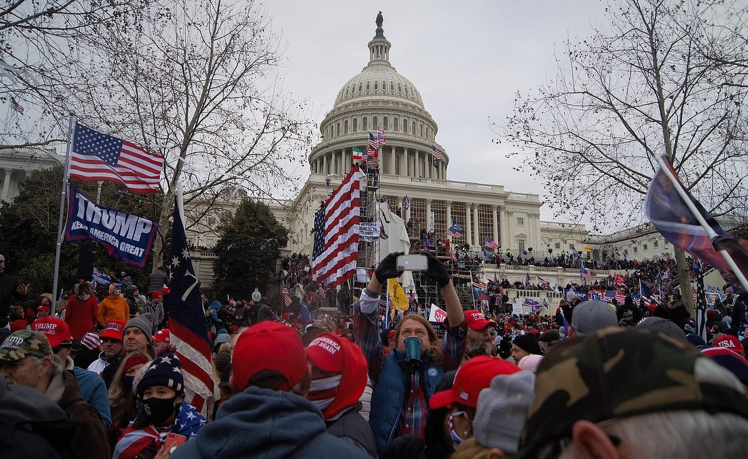 A crowd of protestors, many wearing red hats and waving American flags, is standing in front of the Capitol building. One person is also flying a Trump, Make America Great flag. A white man is holding up his phone to take a video of the scene. Protesters have climbed up the walls of the Capitol.