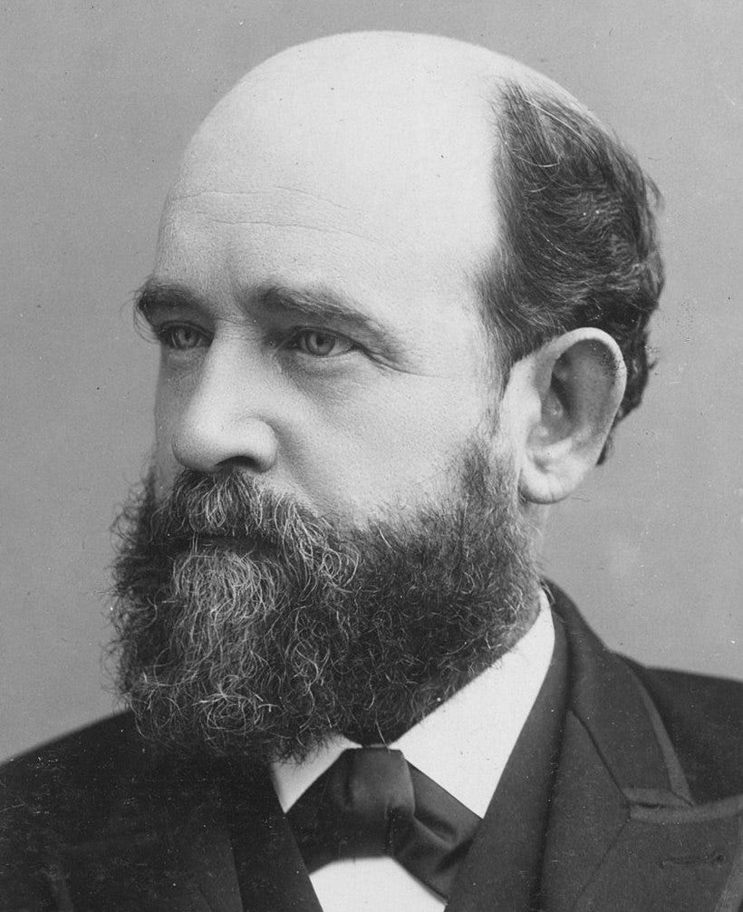 A black and white picture of a balding, bearded white man.