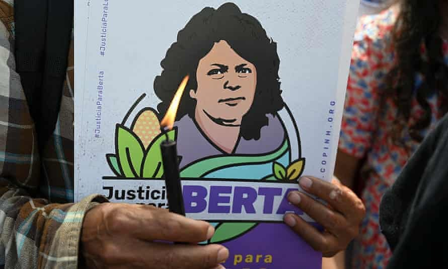 A member of Indigenous rights organisation Copinh holds a candle while waiting for the sentencing of Roberto David Castillo, the businessman found guilty of collaborating in the murder of environmental defender Berta Cáceres.