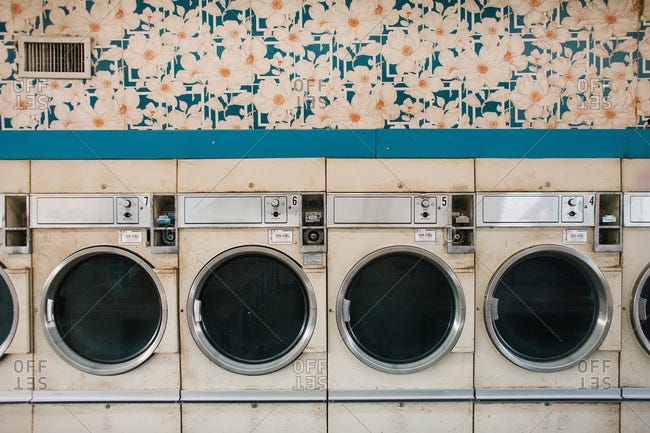 Old dryers in a laundromat stock photo - OFFSET