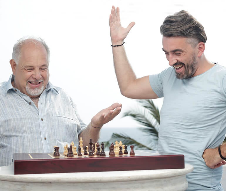 Two white men marvel at the Square Off chess board.