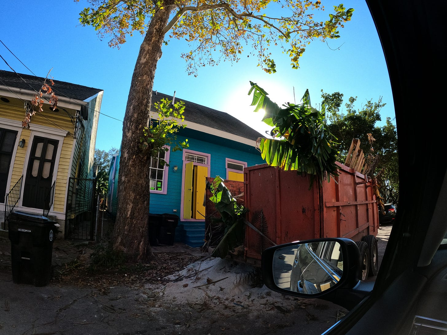 the sun is shining on a colorful blue house with yellow windows as bananna tree stretches out over a dumpster - this is classic shot of Bywater neighborhood in new orleans