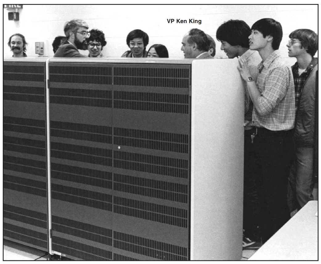 Several people gathered around a mainframe computer that is very large--like two refrigerators.