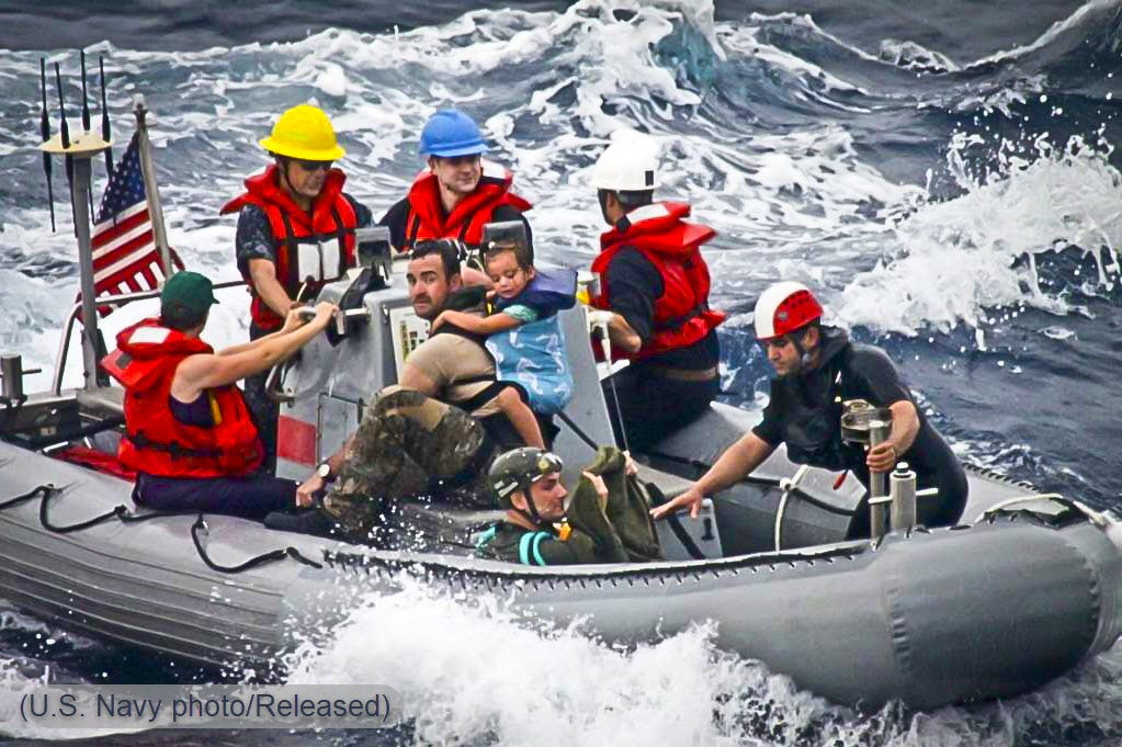 Nine people, including two small children, on a US Navy RHIB amongst high seas in the Pacific Ocean.
