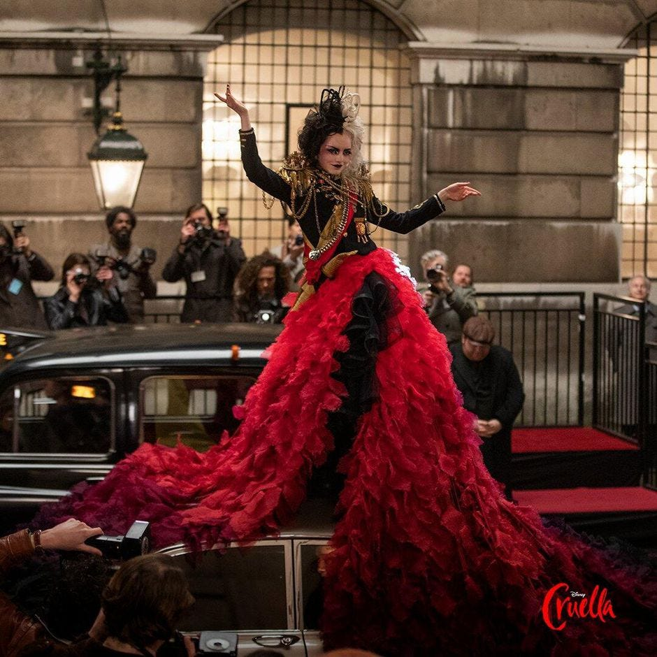 Cruella, played by Emma Stone, is posing with her arms out in a punk, embellished jacket, and flowing red skirt, atop a car in the street, while onlookers photograph her.