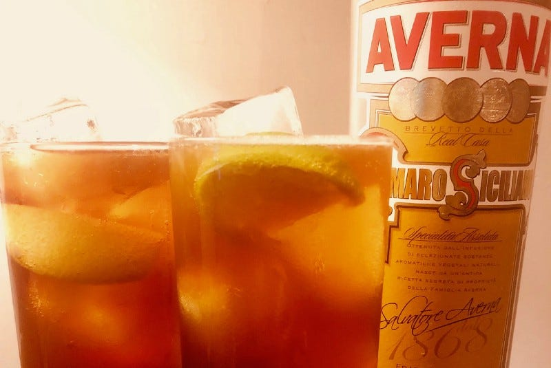 Two glasses full of amber liquid, ice cubes, and lemon slices next to a bottle of Averna amaro.