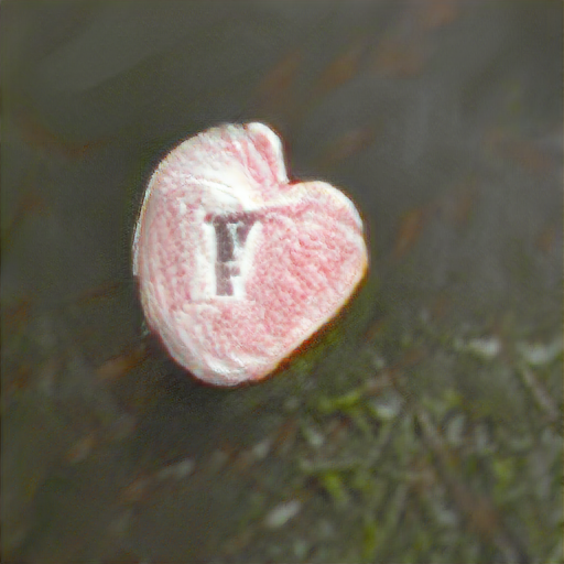 The candy looks sugar-frosted and almost heart-shaped. Printed on the candy is a single black letter that looks like an f with a fishhook top.