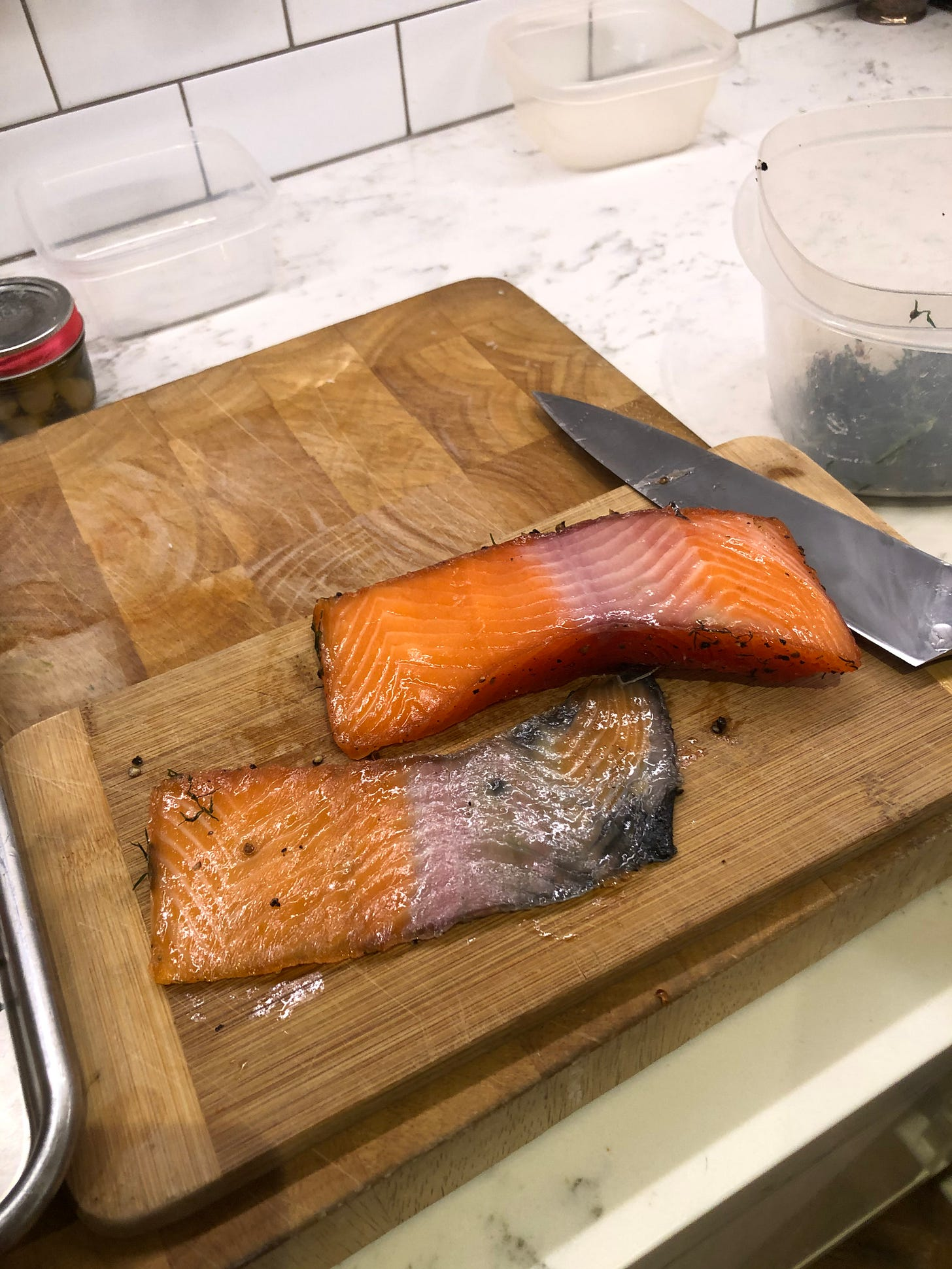 A piece of gravlax with the skin removed. A little flesh remains on the skin.