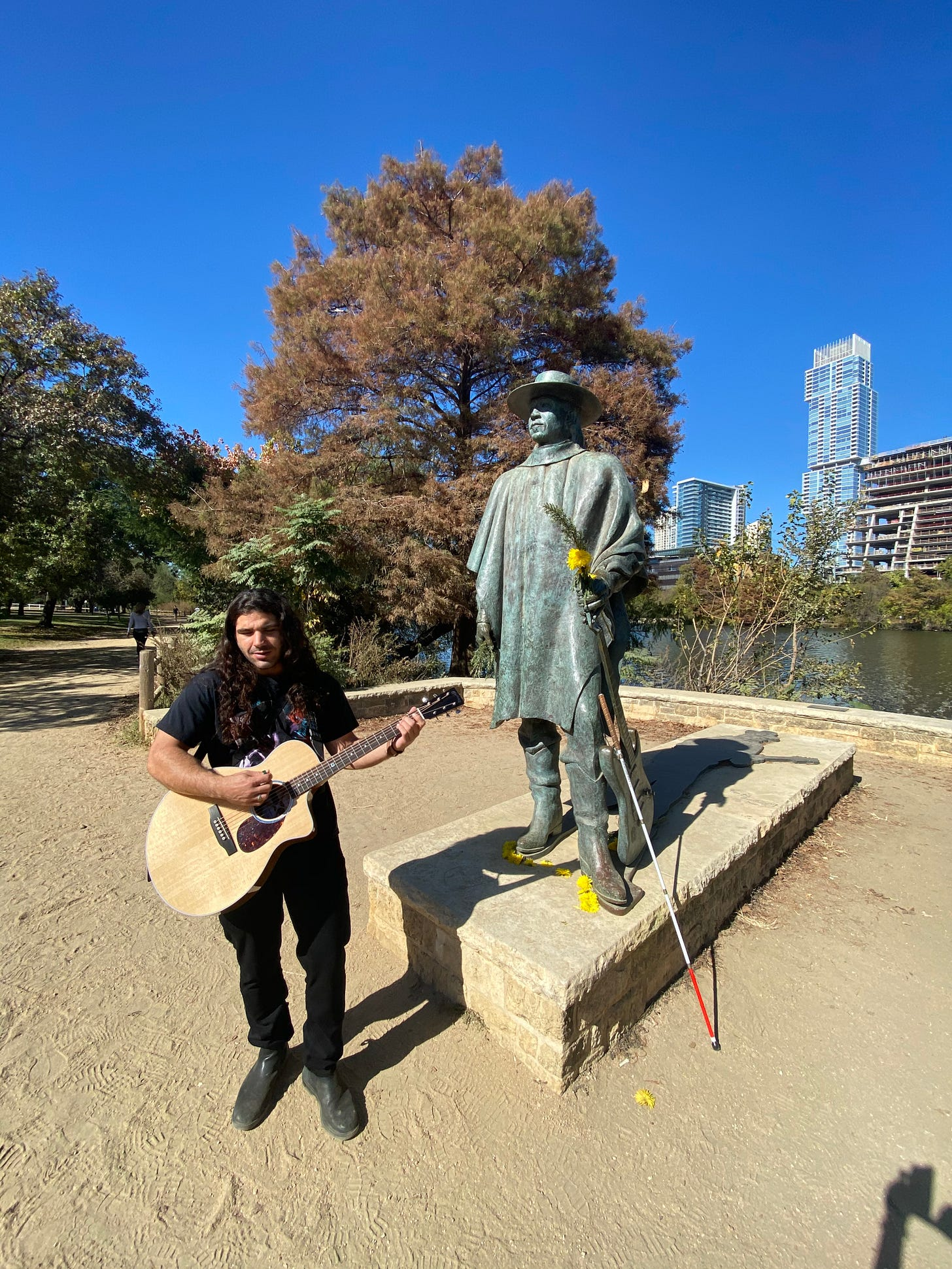 anthony standing in front of the stevie ray vaughn status with yellow flowers on stevies hands -- ant is holding his guitar and smiling up at his hero