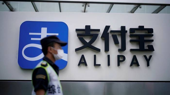 A security guard wearing a mask walks past an Alipay logo at the Shanghai office of Alipay, owned by Ant Group
