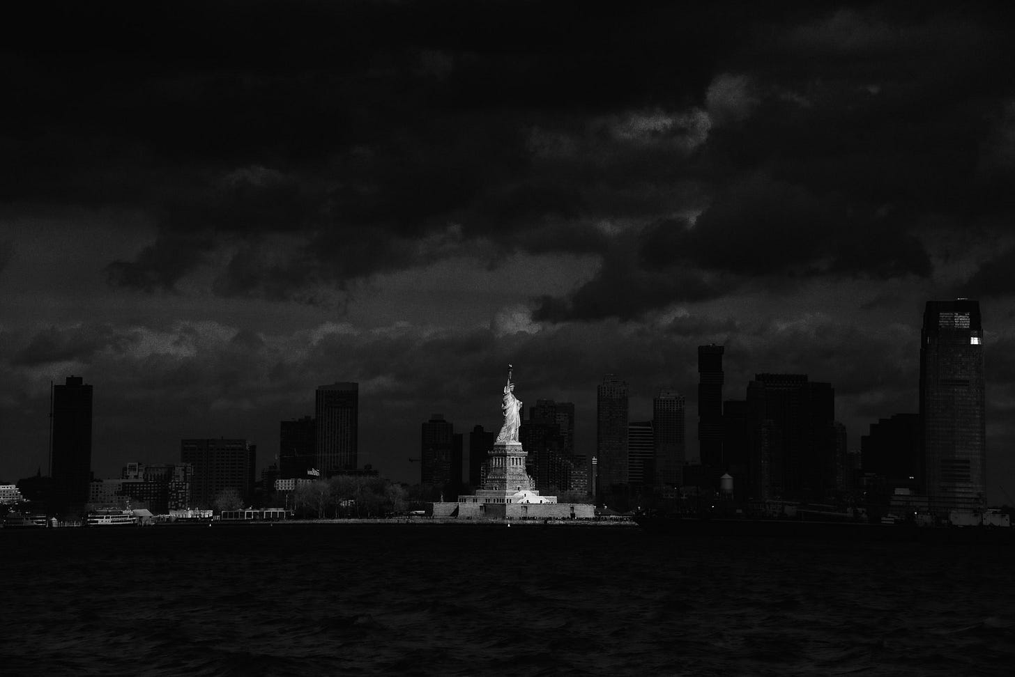 A black and white photo of the Statue of Liberty brightly lit against a dark cityscape.