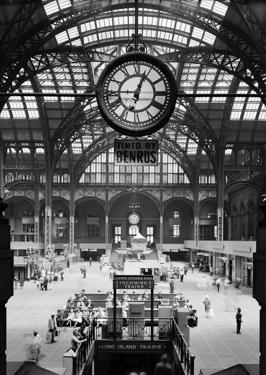 A large clock under a glass dome over the exit concourse