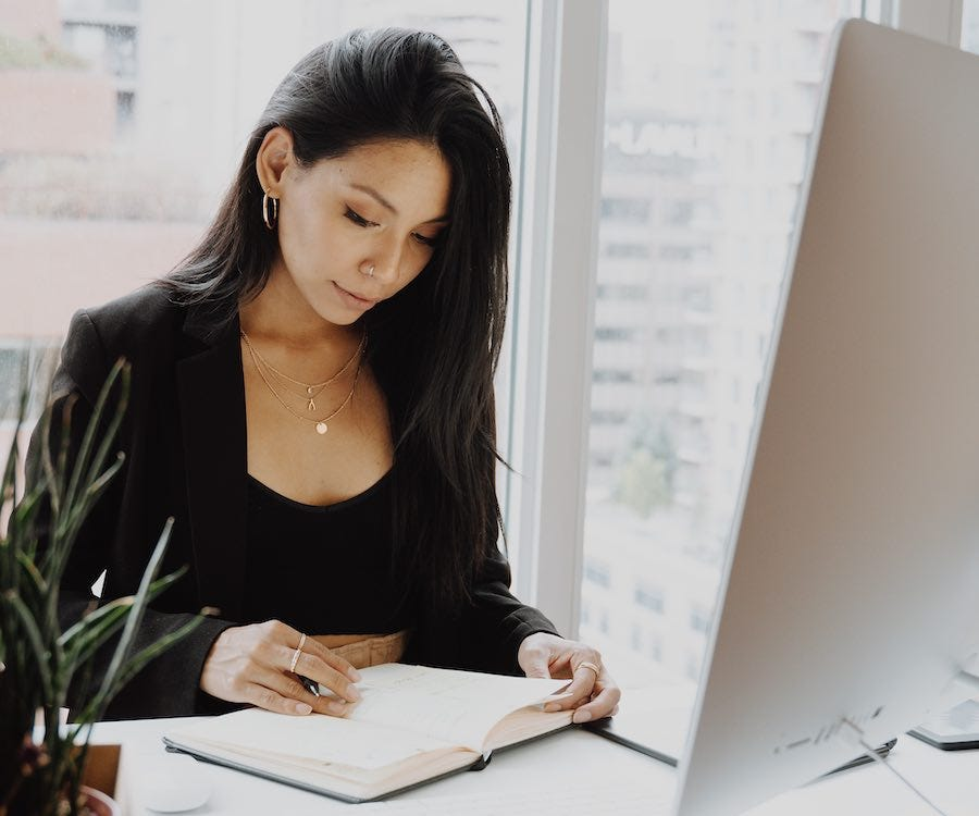 Lady reading her journal in front of computer
