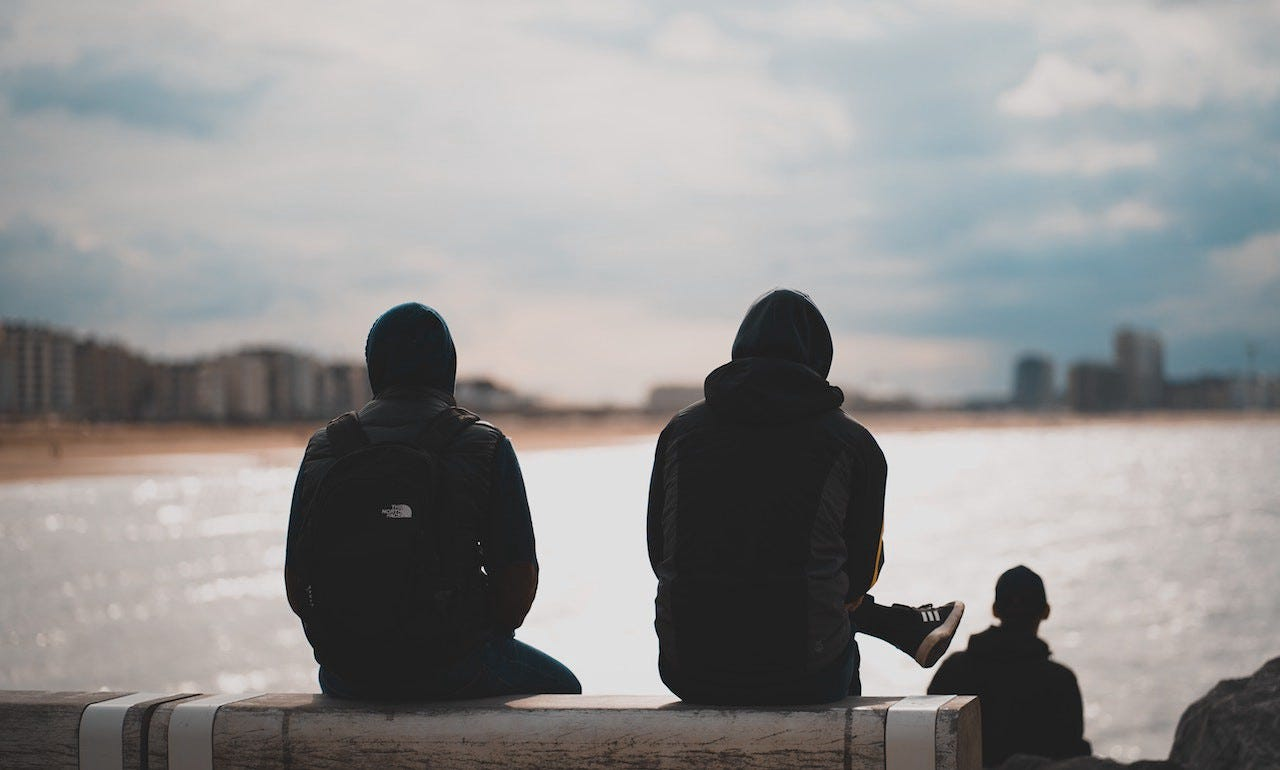 Two guys sitting on a bench looking out to sea for article by Larry G. Maguire