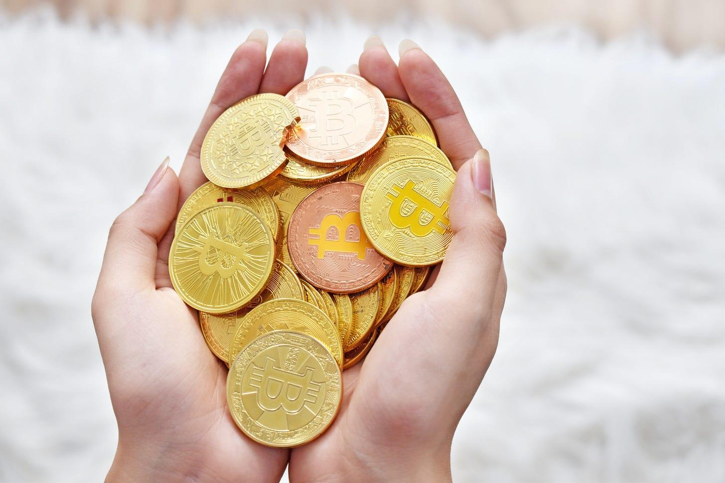 Novelty Bitcoin tokens held in a hand. Via Unsplash