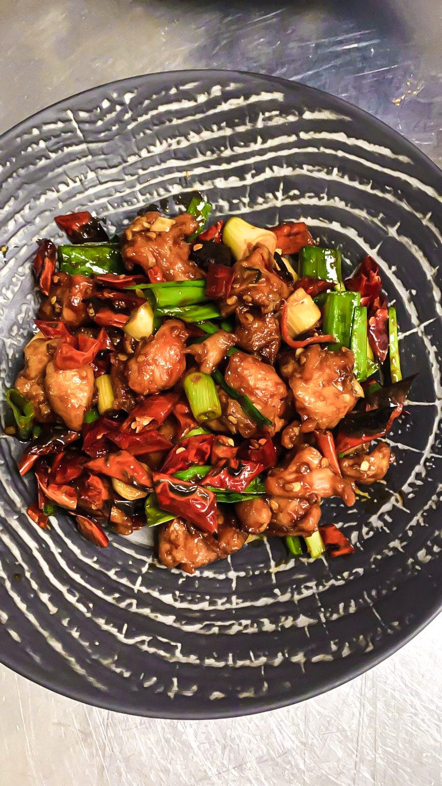 An overhead shot of a dark textured plate in the middle of which is a pile of bite-sized pieces of cooked chicken, spring onions and red chillies.