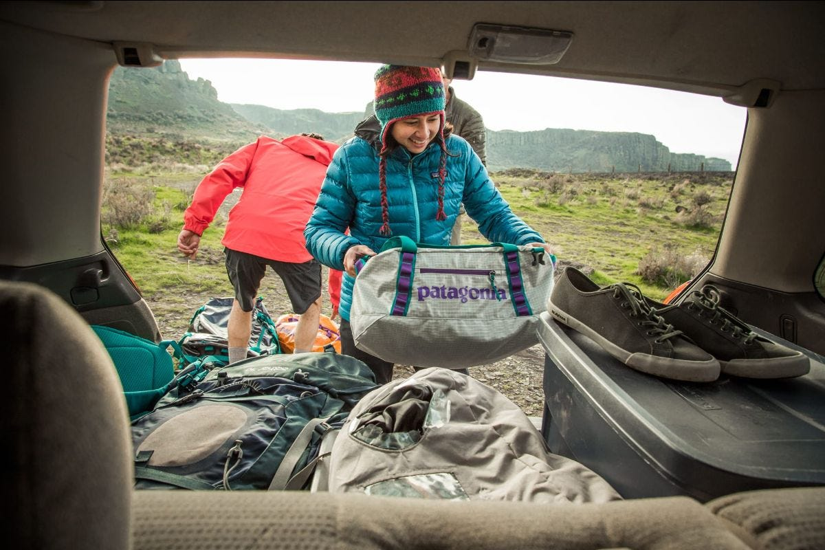 a woman pulls a patagonia black hole duffet out of the trunk of an suv