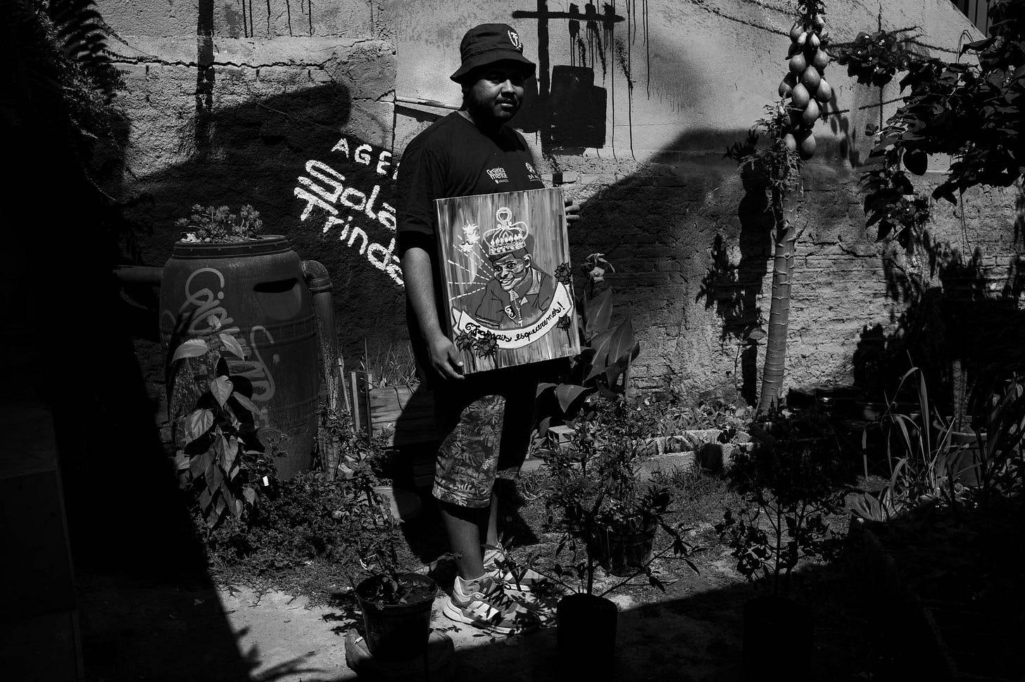 Foto em preto e branco mostra Thiago Vinicius em pé no quintal da agência Solano Trindade segurando uma pintura que mostra um homem com coroa