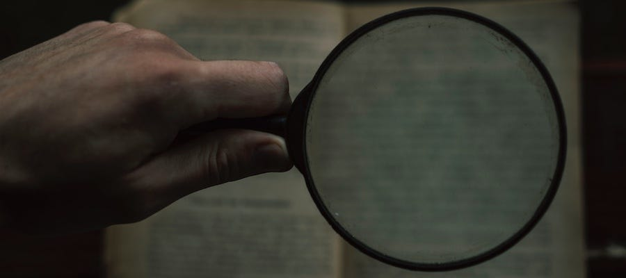 Reading book with magnifying glass
