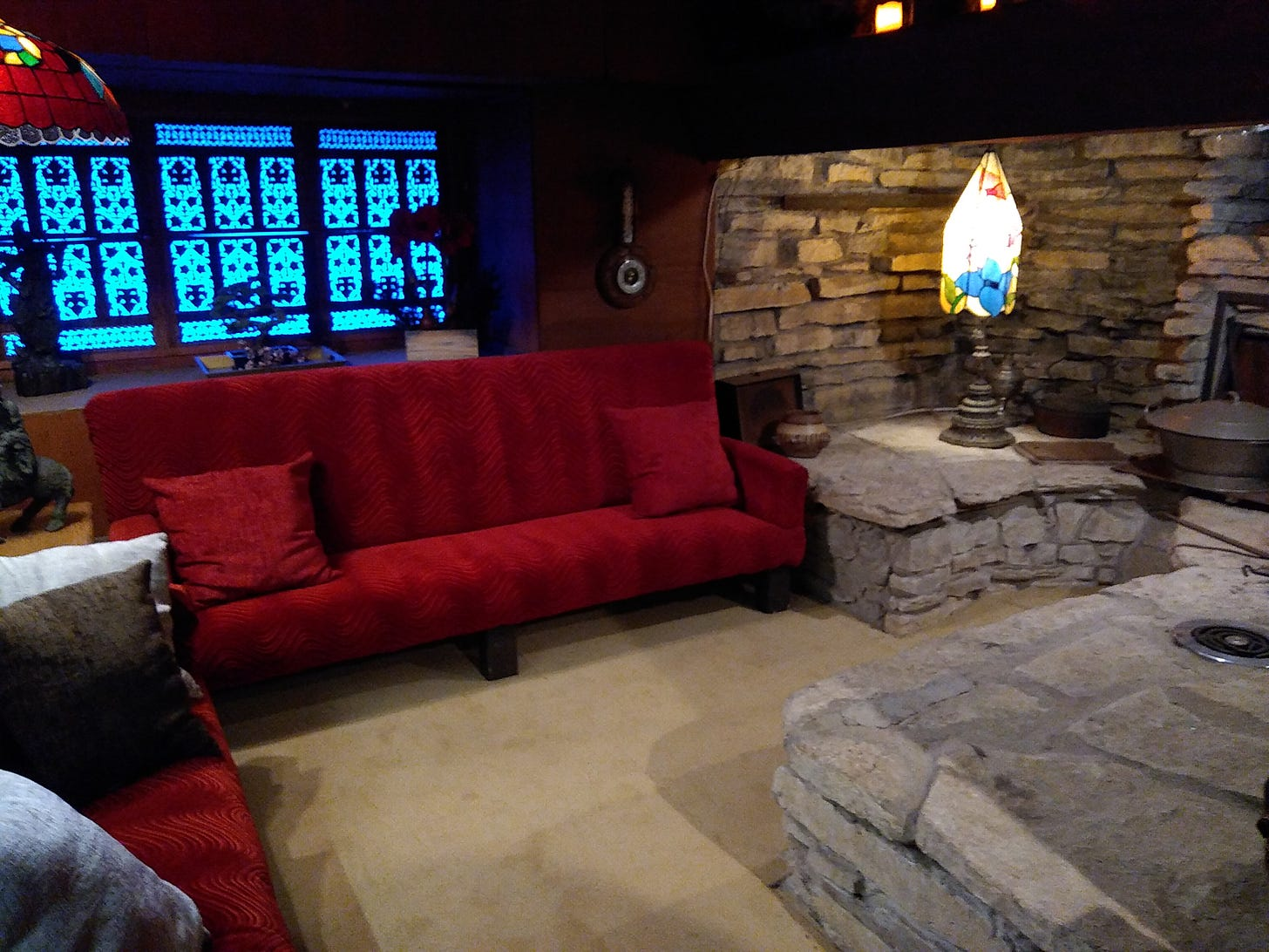 Living room with natural rock brick walls, Indian wooden screen on window, sofa