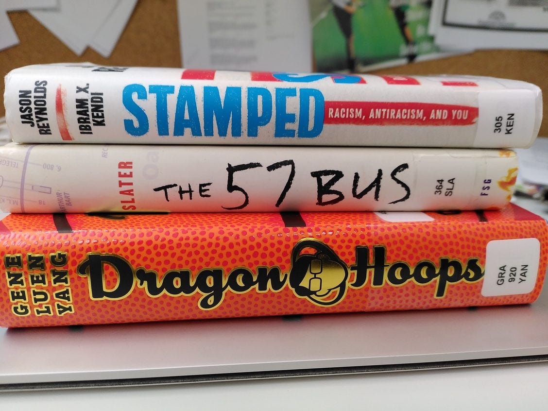 Stack of book spines, Stamped by Jason Reynolds & I. Kendi, The 57 Bus by Slater, Dragon Hoops by G. Yang
