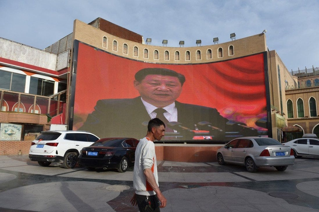 """A man walking past a screen showing images of China's President Xi Jinping in Kashgar in China's northwest Xinjiang region. More than one million ethnic Uygurs and other mostly Muslim minorities are believed to be held in a network of internment camps that Beijing describes as """"vocational education centres. Photo: AFP"""