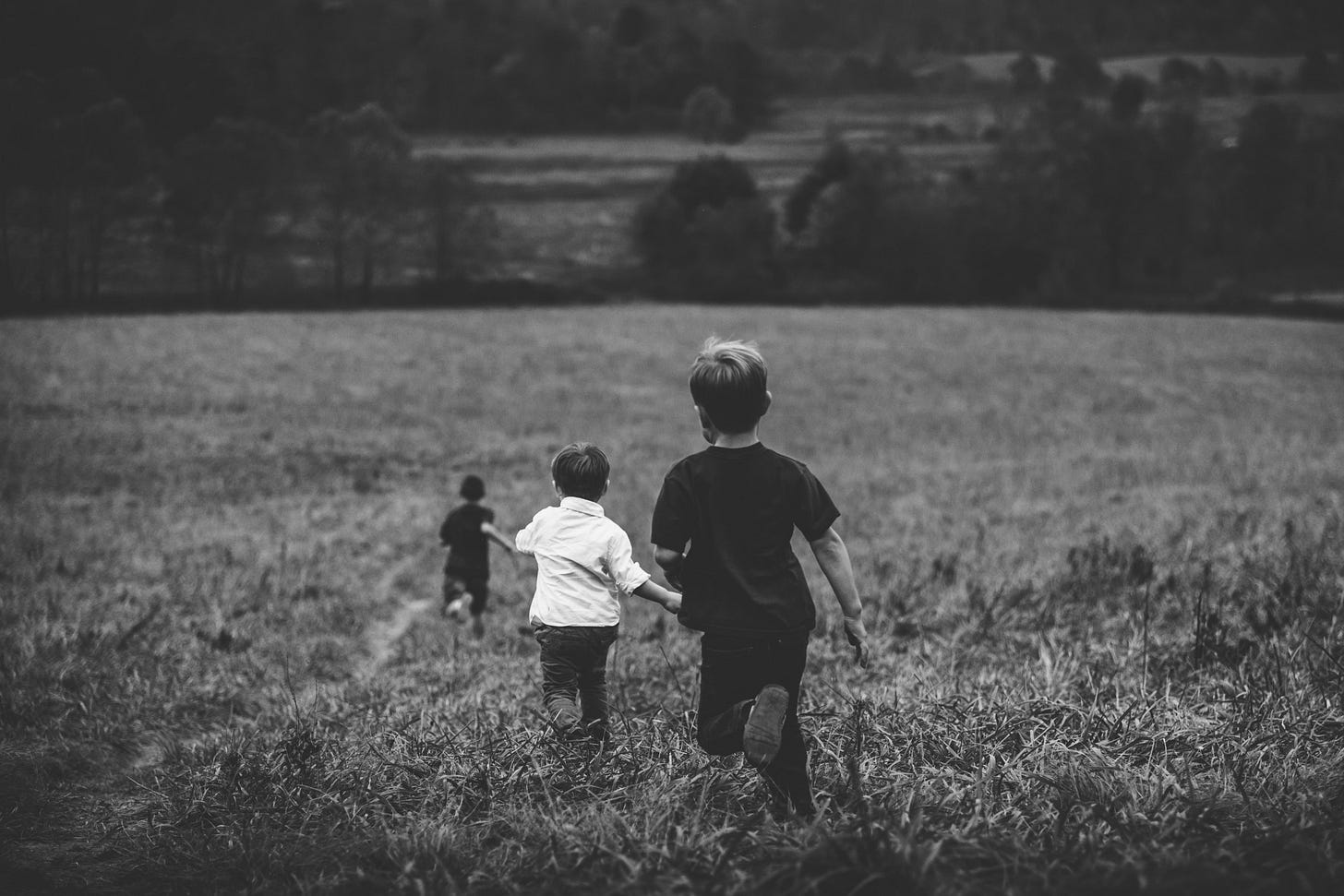 black and white photo of children running in a field for article by Larry G. Maguire