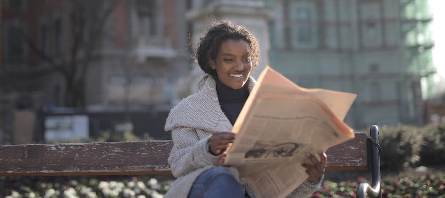 Young woman sitting on bench outside reading newspaper