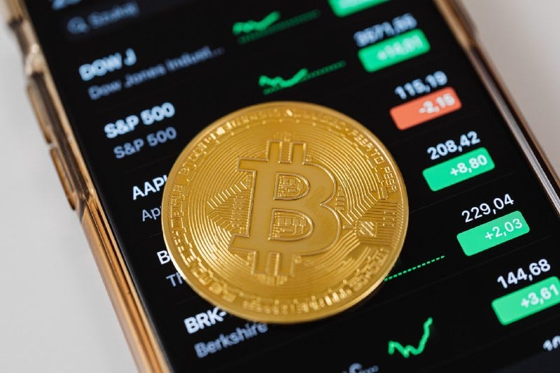 A golden Bitcoin coin on top of a cell phone displaying stock prices.