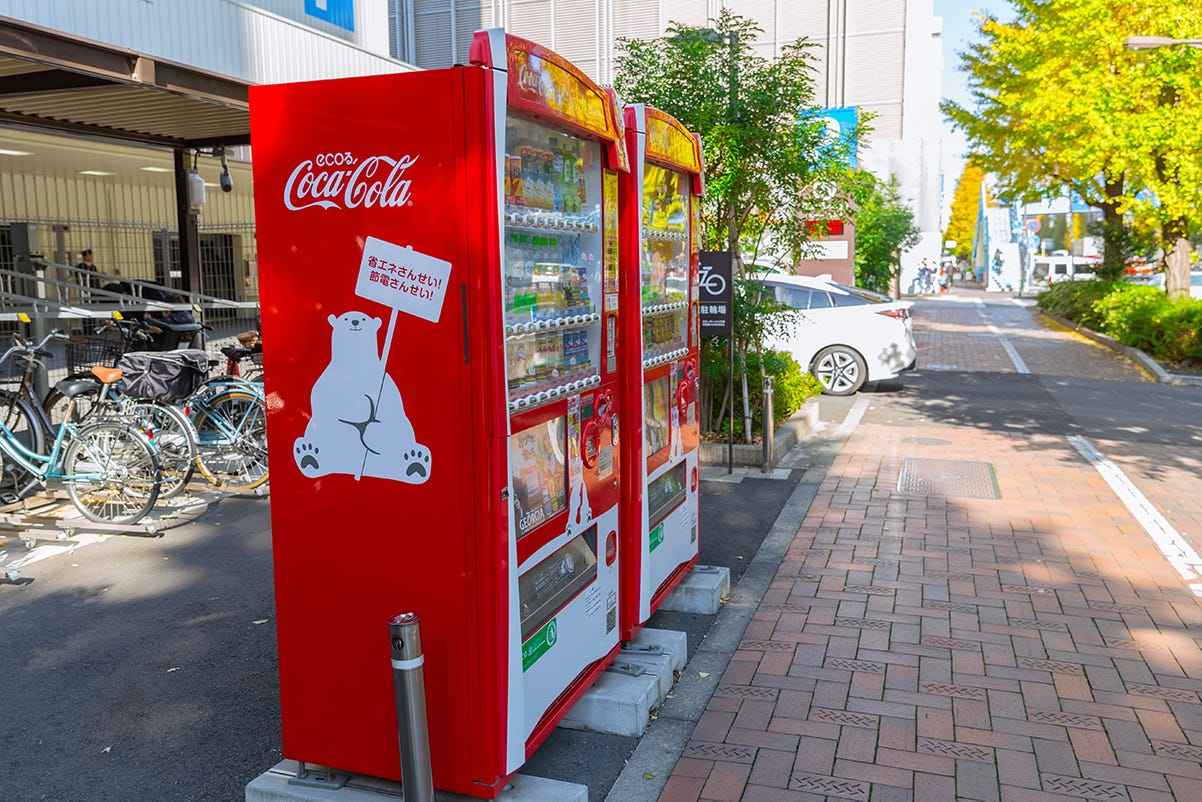 A red vending machine on the sidewalk  Description automatically generated with low confidence
