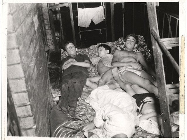 """""""View of members of a family as they sleep outside on the fire escape of their tenement building, July 27, 1940."""" (Photo by Weegee [Arthur Fellig] / International Center of Photography)"""