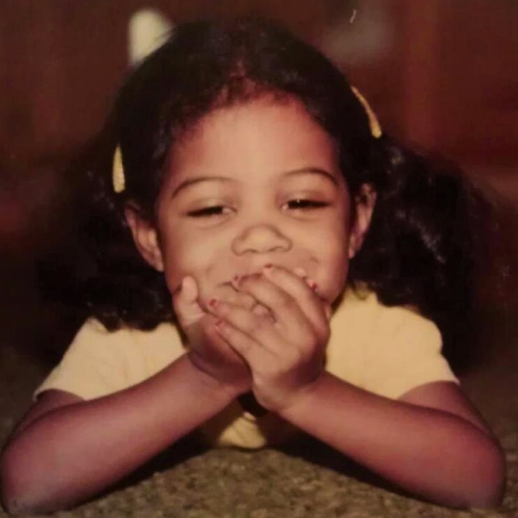 Photo of Patricia as a young child. She is laying on the floor, propped up on her elbows. Her hands cover her smiling mouth. Her fingernails are painted red. She wears a white shirt and has barrettes on each side of her head.