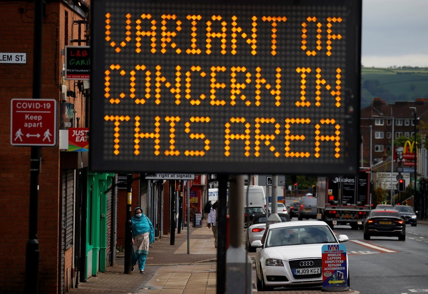 A woman walks past an information sign amid the outbreak of the coronavirus disease (COVID-19) in Bolton, Britain, May 17, 2021. REUTERS/Phil Noble