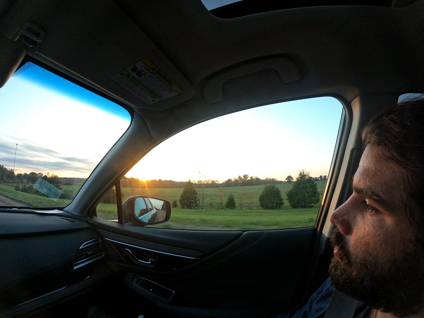 Anthony staring out the window as the sun sets over a green field in the Mississippi Delta