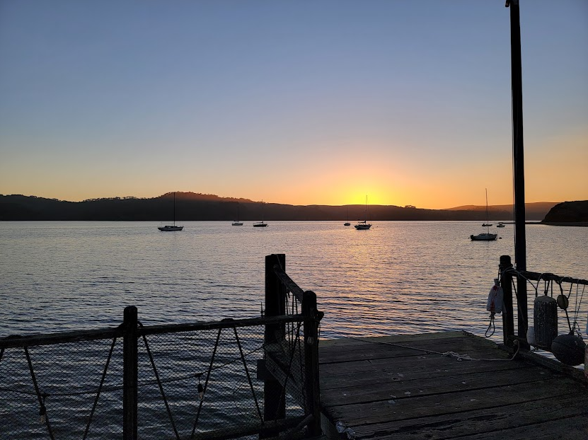 Photo of the sun setting over low hills. In the foreground is a bay with 8 sailboat silhouettes. Closest foreground has a wood deck.