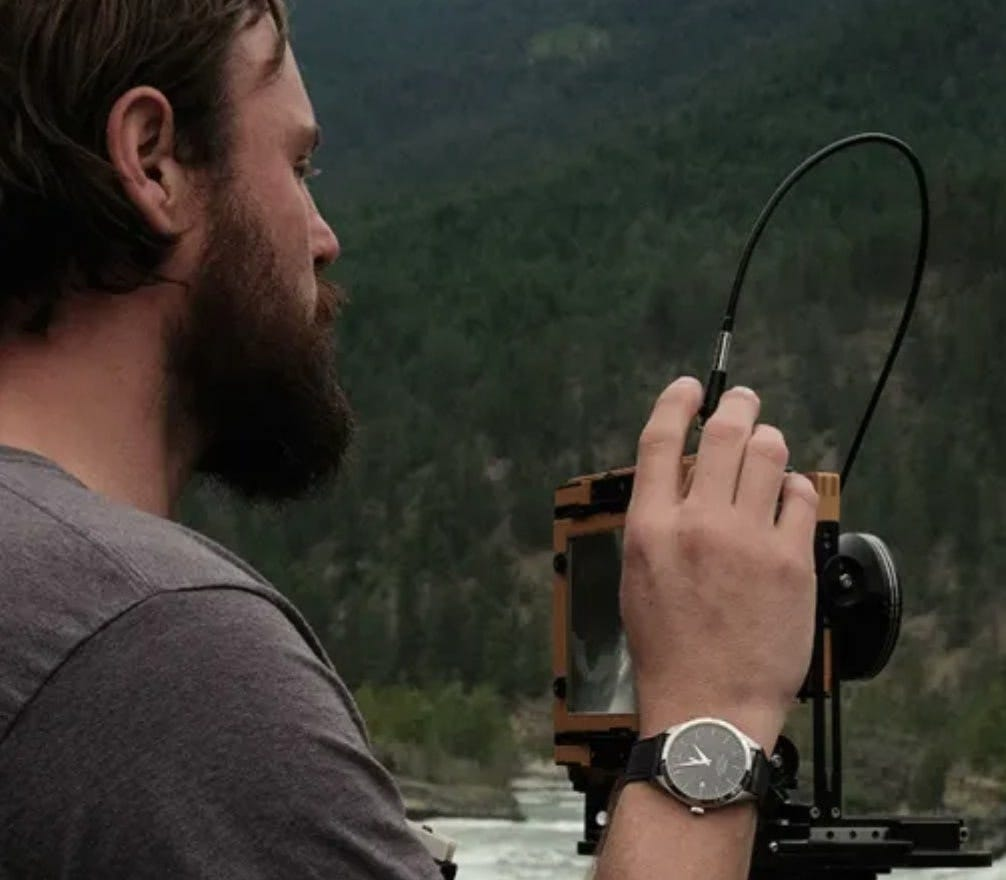 bryan schutmaat wearing the Timex american documents watch while he takes a photo of a river