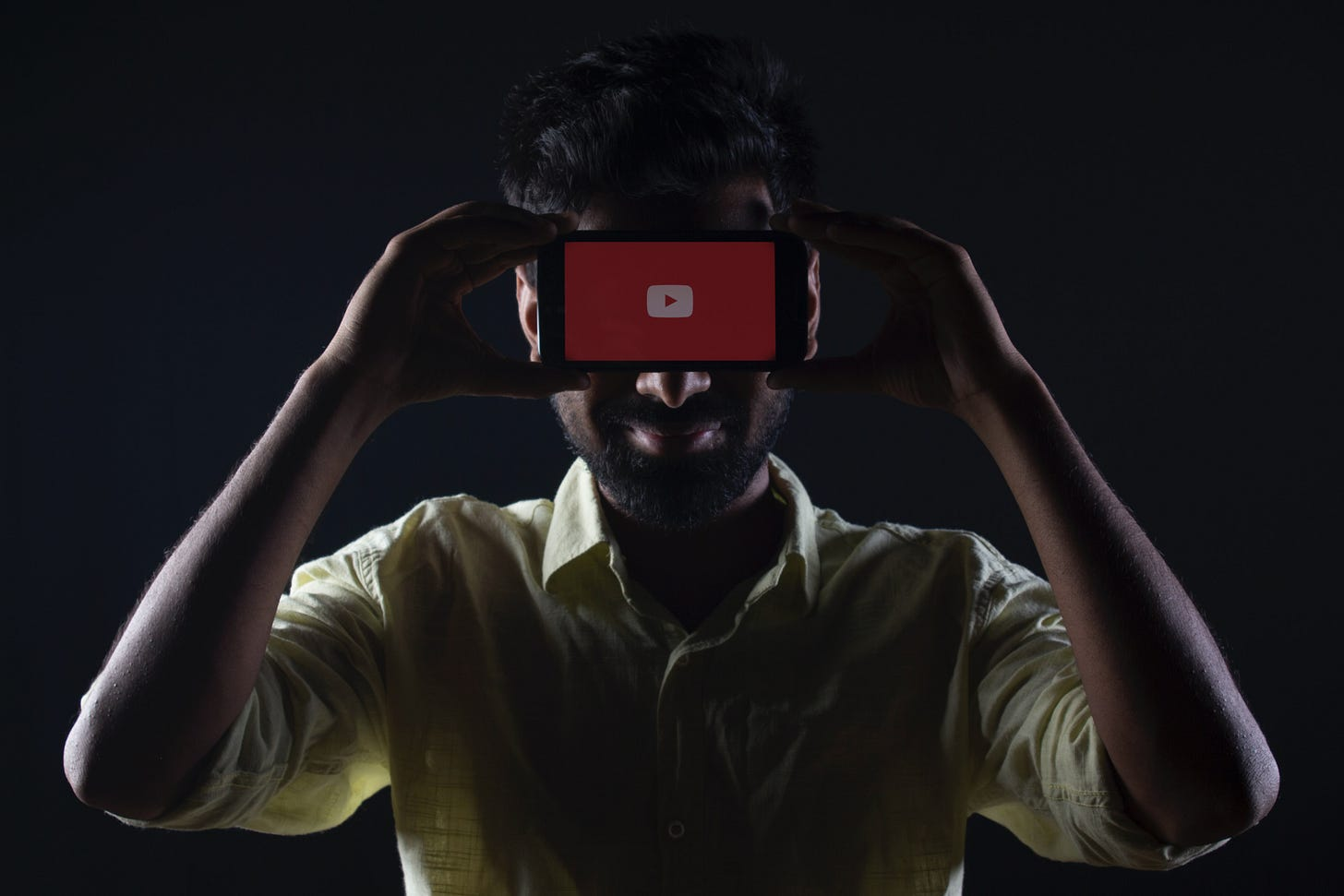 A man holds a phone showing YouTube's logo on his forehead. Photo by Ratchit Tank / Unsplash