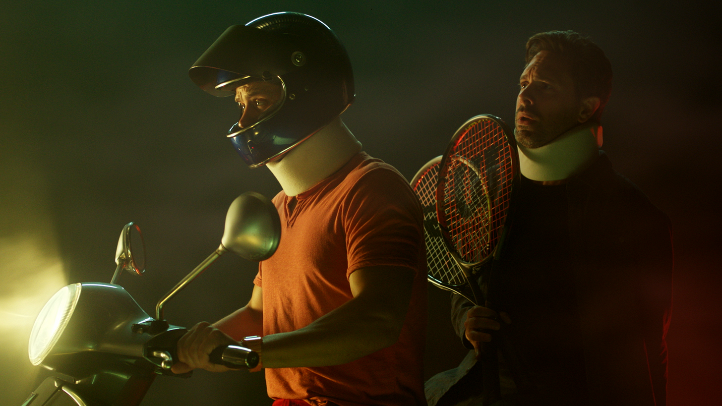 From 'The Mimic': A writers, holding two tennis rackets, rides on the back of a vespa with a man wearing a helmet.