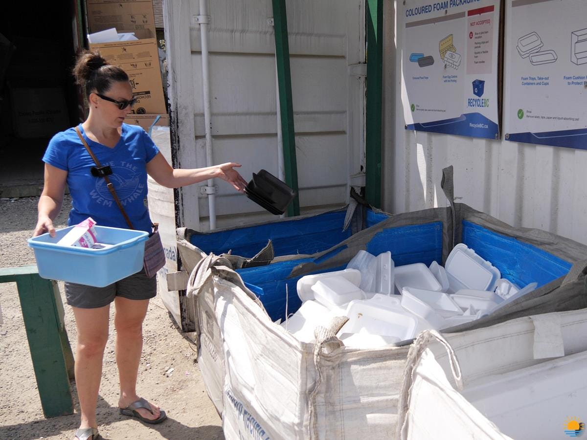Brunette woman in shorts dropping off her recycling at the local recycling depot.