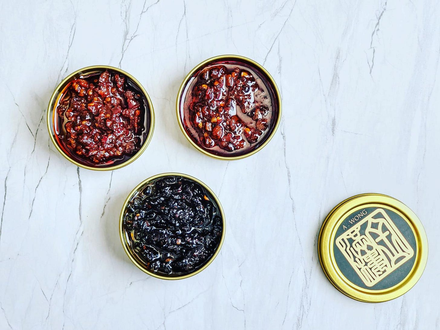 An overhead shot of three open tins of sauces and a tin lid on a marble tabletop