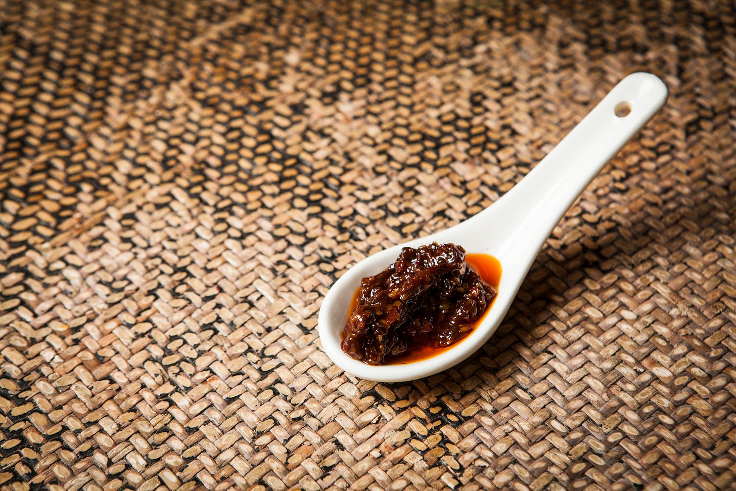 A white ceramic spoon rests on a rattan table mat. In the bowl of the spoon is a deep-reddish brown relish.