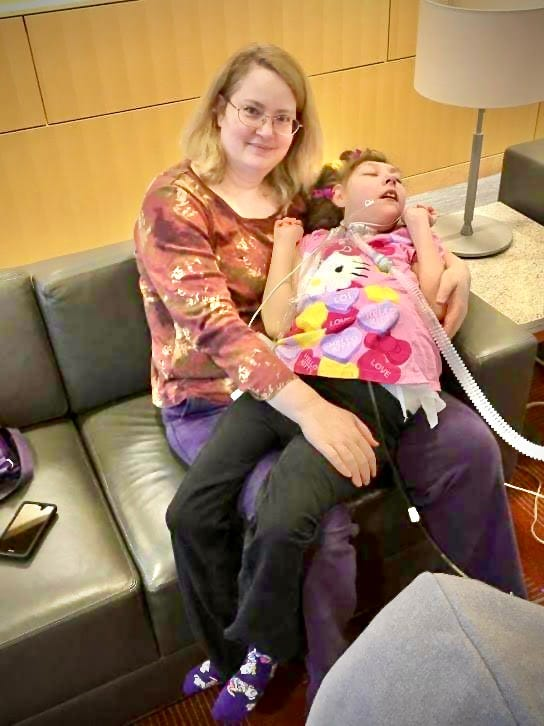 A blond white woman with glasses smiles at the camera while sitting with a teenage girl on her lap. The girl has a bright pink Hello Kitty shirt on as well as a tracheostomy tube and a g-tube.