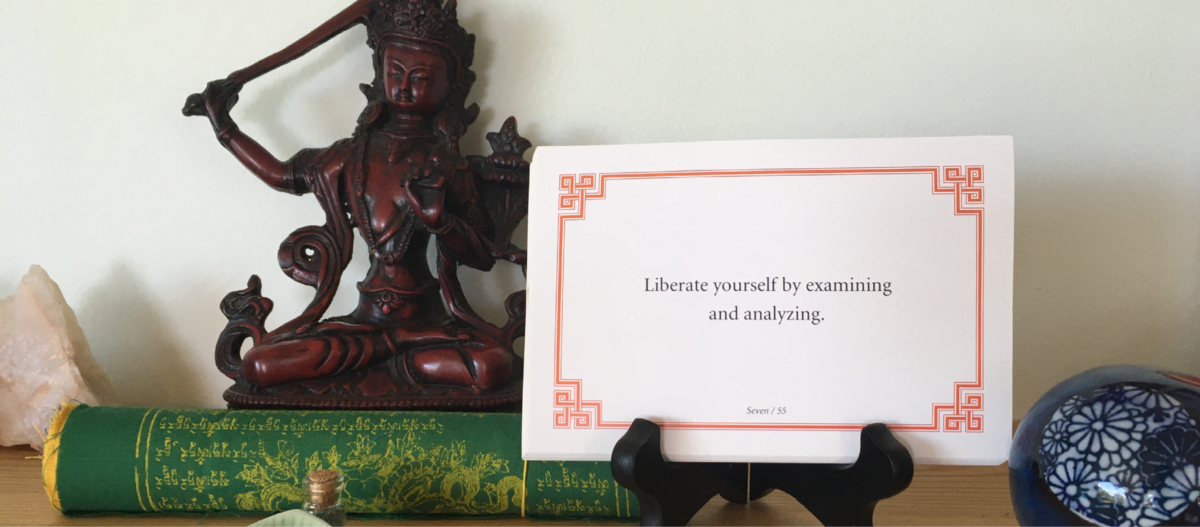 """A Lojong card that reads """"Liberate yourself by examining and analyzing"""" sits on a wooden shrine, to the right of a statue of the Bodhisattva Manjushri."""