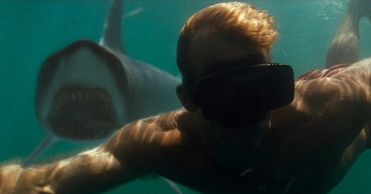 A man swimming underwater towards the camera. Over his shoulder is a shark with its mouth open turning towards him.