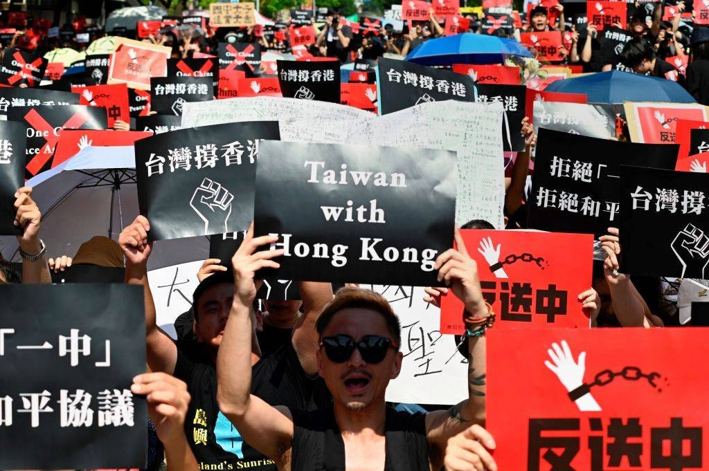 People in Taipei display placards during a demonstration in support of the continuing protests in Hong Kong on June 16, 2019.