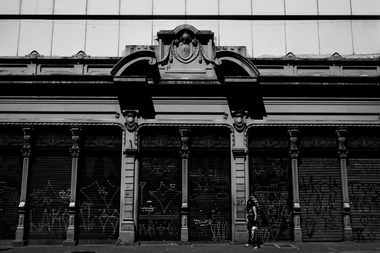 Pórtico antigo no centro de São Paulo com portas de metal abaixadas, imagem em preto e branco.