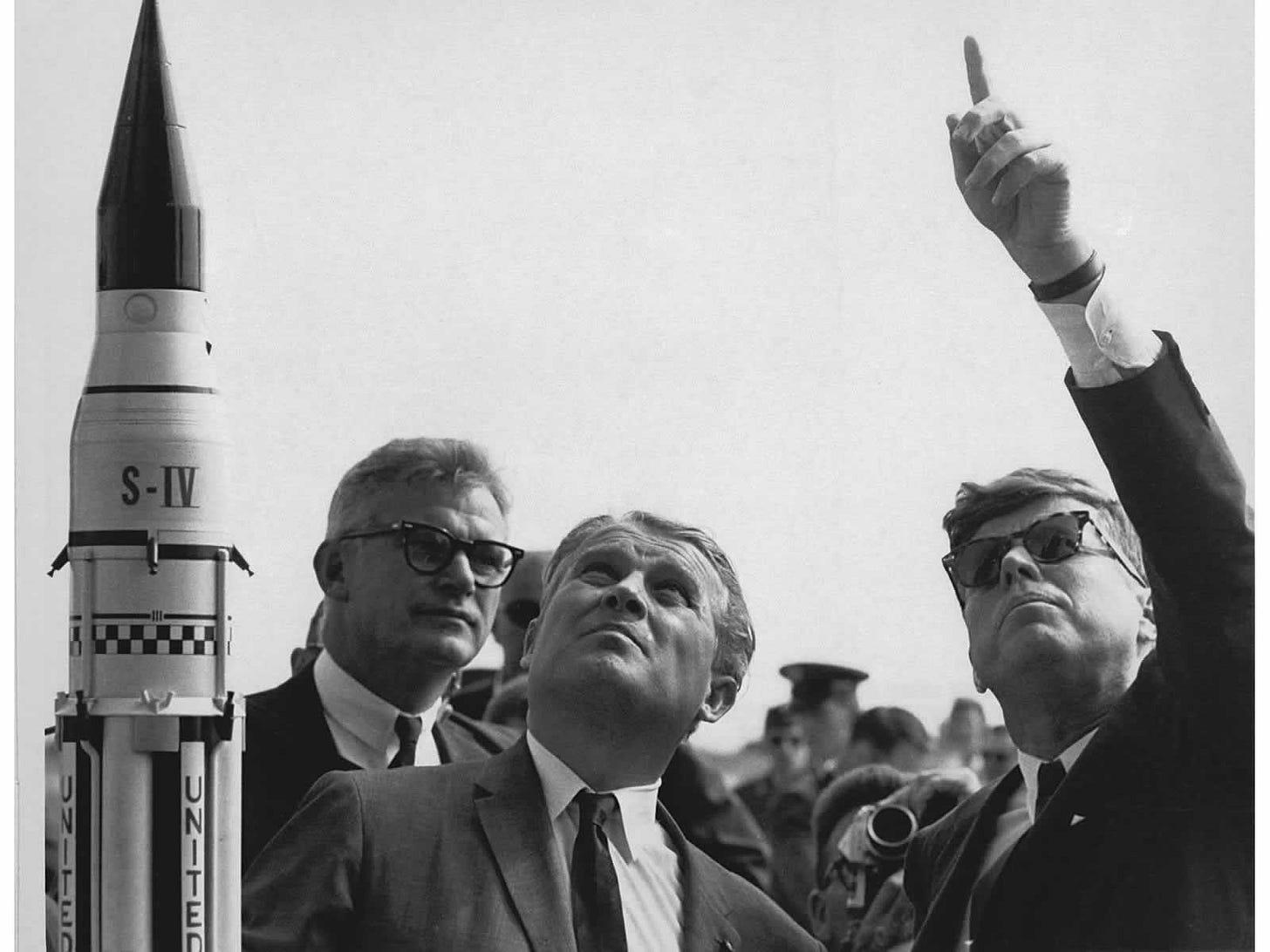 Photograph of JFK pointing skyward