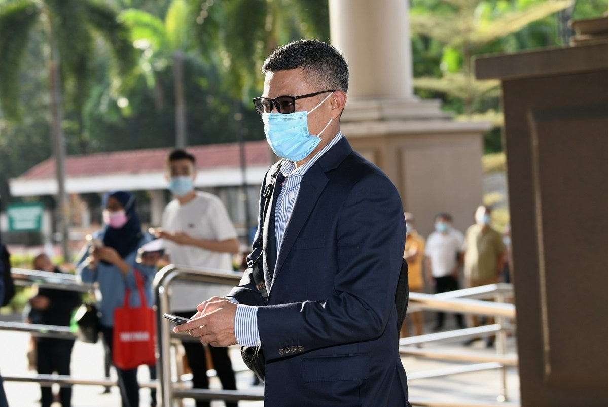 Former 1MDB CEO Mohd Hazem Abdul Rahman holding his smartphone at the Kuala Lumpur Court Complex this morning. (Photo by Shahrin Yahya/The Edge)