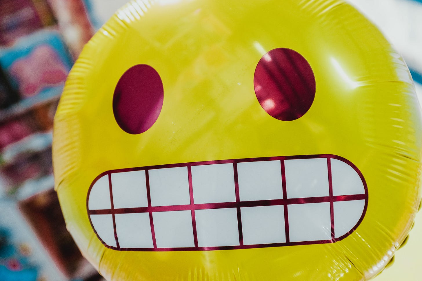 Photo of a ballon in the shape of a grimacing emoji. (Bernard Hermant / Unplash)