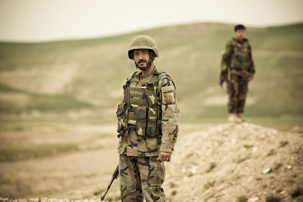"""4540561318_c4eff90633_o, Two Afghan soldiers stand watch while a convoy passes in Faryab Province, Afghanistan. The Norwegian Operational Mentor and Liaison Team mentors the 3rd Kandak in Faryab Province, Afghanistan."""" by ResoluteSupportMedia (ISAF Public Affairs) is licensed under CC BY 2.0, no changes were made."""